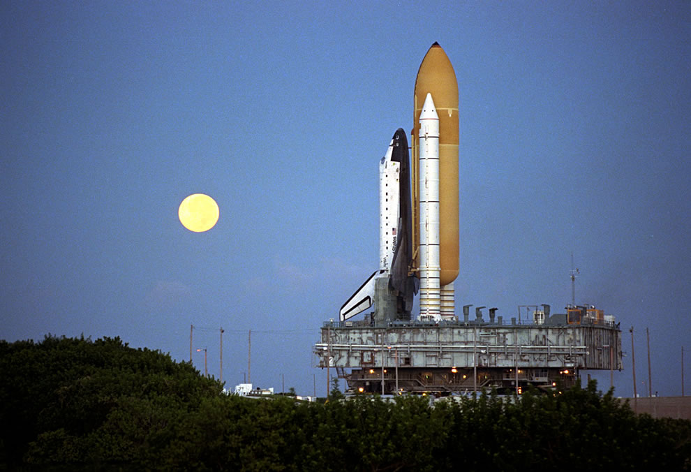 Shortly-before-dawn-a-red-rimmed-moon-helps-to-light-the-way-for-the-Space-Shuttle-Atlantis-as-it-rolls-out-to-Launch-Pad-39A-in-preparation-for-launch-of-Mission-STS-86