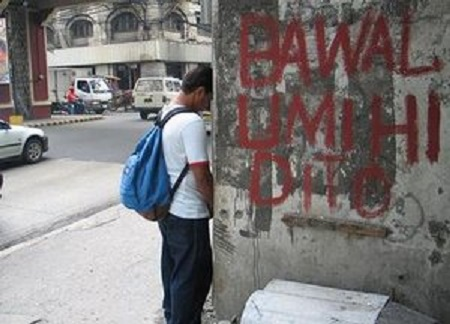 Man-urinating-beside-a-bawal-umihi-dito-sign-in-the-Philippines